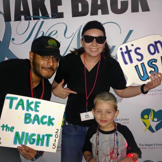 The Rape Crisis Center's Jameson Cardenas and Amanda Cuellar take to the step-and-repeat with a young San Antonian during Take Back the Night 2015.